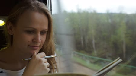 autor : Dolly close-up shot of a young thoughtful woman making notes sitting by the window in moving train