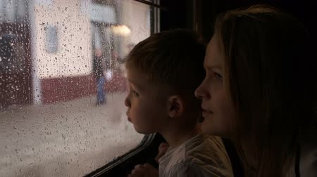 utazó : Young mother and her little son in the train looking out the window on a rainy day while passing the station Stock mozgókép