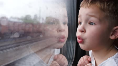 utazó : Close-up shot of a little curious boy looking out of the window in train. Its raining outside, child reflecting in the glass