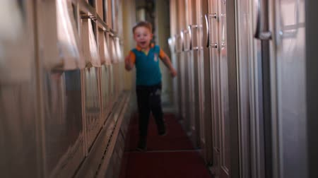 прихожая : Happy little boy running along the train hallway