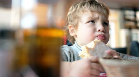 одиноко : Close-up shot of a cute little boy eating a bun in a cafe Стоковые видеозаписи