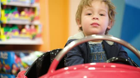 toy : Little boy riding a toy car in the toy store. He swinging in the car and calling his mom Stock Footage