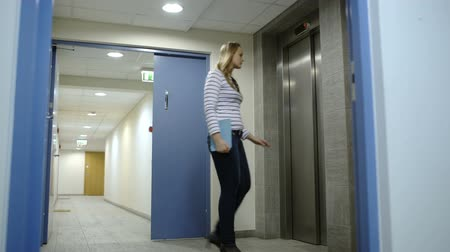 Войти : Young woman coming to the elevator, calling it, waiting and entering the second one when it coming Стоковые видеозаписи