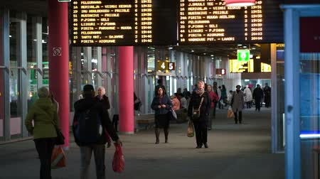 chegada : TALLIN, ESTONIA - MAY 25, 2014: People walking on Central bus station with digital display with routes above Vídeos