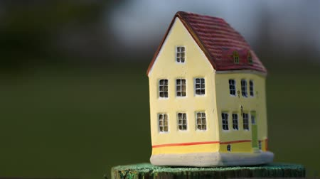 zabawka : Hand putting a  toy house on small stub on blurry natural background. Real estate, country house or mortgage symbol
