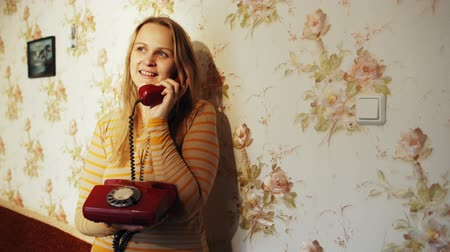 falar : Dolly shot of a smiling young woman having a phone talk at home. She standing leaning on the wall