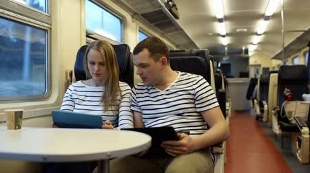 ekspres : Man with laptop talking to the woman using laptop. They traveling by train in the evening Stok Video