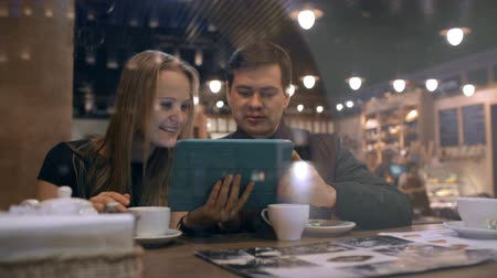 ресторан : Young man and woman in a cafe looking on the touchpad and talking vividly