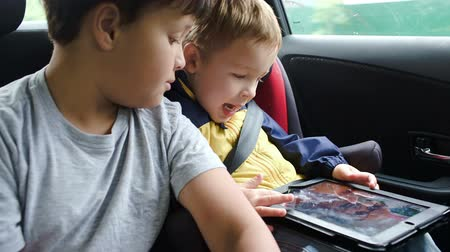 ülés : Two boys using touchpad in a moving car. Younger boy sitting in child safety seat Stock mozgókép