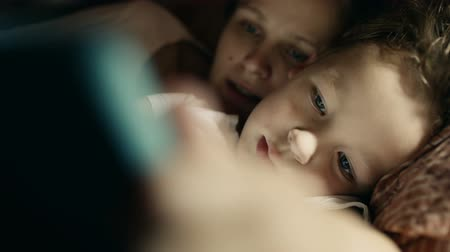 время ложиться спать : Close-up shot of son and mother in bed playing game on touch pad. Bedtime entertainment
