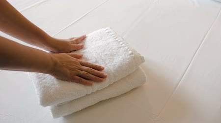 toalhas : Close-up shot of woman putting two fresh clean towels on the bed with white sheet