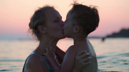мама : Mother throwing up a little son in the se at sunset. Family fun in water