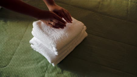 towel : Woman putting a pile of clean white towels on the bed and smoothing it with hands