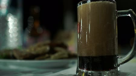 паб : Close-up shot of pouring dark beer with a lot of foam into big glass mug Стоковые видеозаписи