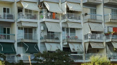 навес : Panning shot of hotel facade with sheds on balconies. Summer vacation