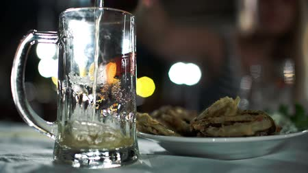 cerveja : Close-up shot of pouring light beer with a lot of foam into glass mug next to plate with fried fish