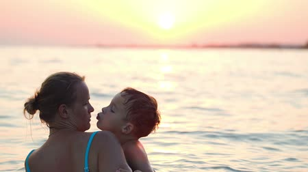 mother love : Young mother and little son swimming in sea at sunset. Boy kissing his mom Stock Footage
