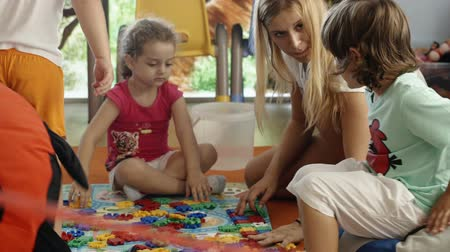 przedszkole : THESSALONIKI, GREECE - AUGUST 22, 2014: Children and schoolmaster doing puzzle in game room or nursery. Little boy bringing big soft ladybug and sitting on it Wideo