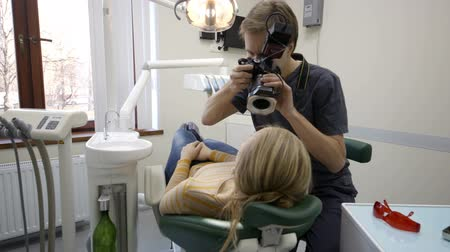 фото : Dolly shot of dentist in clinic making photo of the patients smile and showing it to her Стоковые видеозаписи