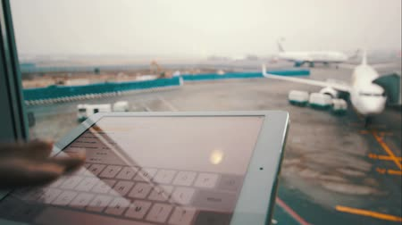odeslat : Close-up shot of woman hand typing on pad by the window with two airplanes can be seen there
