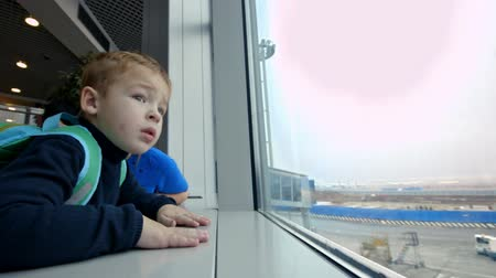 lounge : Little son and mother at the airport. They looking out the window and pointing at something outdoor