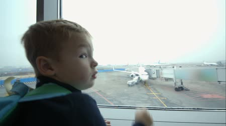 lounge : Little boy looking out the window at the airport and pointing at the plane on takeoff strip