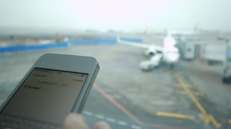 mensagem : Close-up shot of female hand typing text message on smart phone by the window, airport area and plane in background