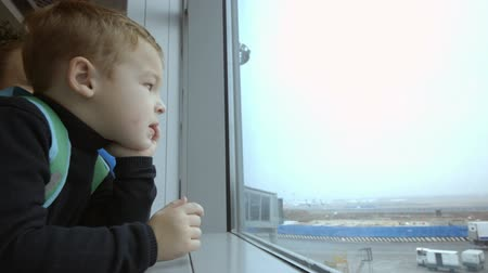 points of interest : Emotional little boy and young mother looking out the window at airport and pointing at something