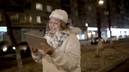kaydırma : Steadicam shot of a happy woman walking with touch pad along city street in cold evening
