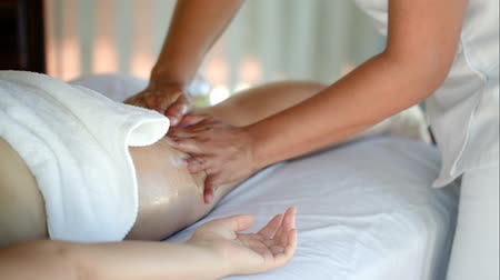 terapeuta : Close-up shot of professional massage therapist making a hip massage in beauty spa. Body and health care