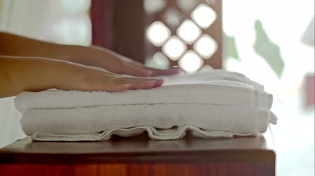 towel : Close-up shot of female hands putting fresh white towels with pink flower on small table at beauty spa