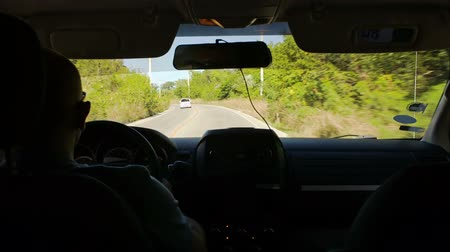 otoyol : Time lapse of car driving on the motorway, then in the countryside on summer day. Driver tells someting and gesticulates. View from inside