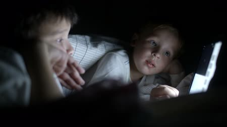 Two little boys in bed try to watch the film at night using the tablet 影像素材