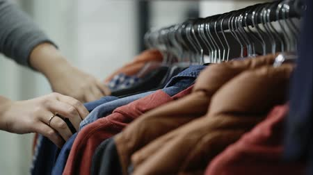 sem camisa : Woman in the shop looks through the male jackets and shirts, which are hanging on the racks
