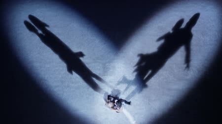 paten yapma : Top view of couple on the ice standing in heartshape spotlights, they starting romantic dance and their shadows reflecting on the ice Stok Video