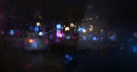 Close-up shot of wet and weeping window of a car moving in the city at night. Female hand wiping it, blurred lights and passing cars can be seen