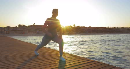 morning : Steadicam shot of young woman doing lunge during her morning exercises outdoors. She is lighted by rising sun. Stock Footage