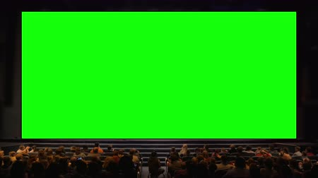 divadlo : Viewers sitting in front of a big chroma key screen in the auditorium. Audience applauding, light going down