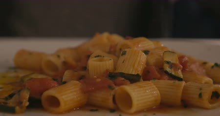 dish : Close-up shot of eating delicious pasta dish with tomato sauce and zucchini. Dinner in cafe or restaurant Stock Footage
