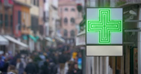 çapraz : Outdoor pharmacy banner with led green cross hanging on the building. Defocused crowd of people walking in the street in background