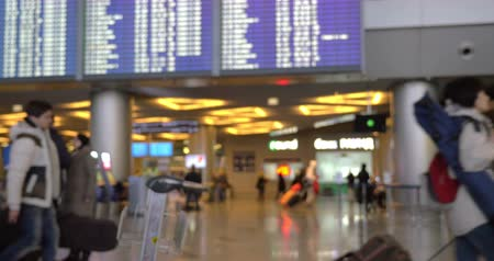 lounge : Everyday routine at the airport. Slight defocus of people walking around, digital flight schedule above