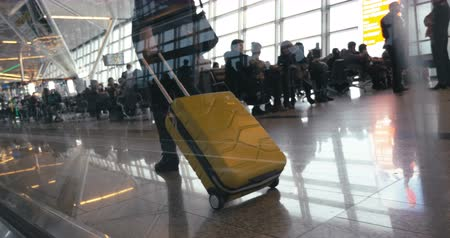 Steadicam low angle shot of a woman walking along the crowded airport lounge with trolley bag. View through the glass