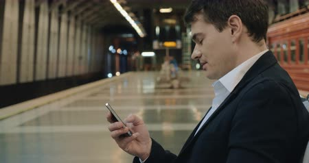 platforma : Young businessman in underground. He sitting and typing text message while waiting for the train. Station platform in background
