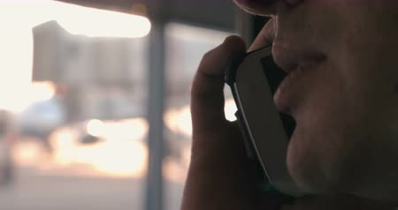 falar : Close-up shot of a man having a phone talk at the airport. Blurred window in background