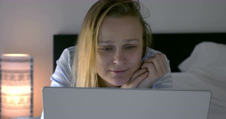 novela : Young woman with laptop lying in bed in the evening. She watching movie triggering emotions of sadness and laugh
