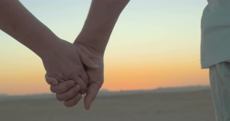 drží se za ruce : Steadicam close-up shot of romantic couple holding hands on the beach against evening sky background