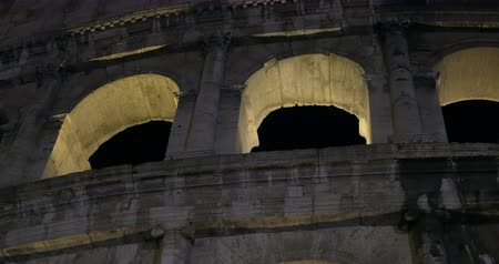 roma : Dolly, close-up and low angle shot of Roman Colosseum illuminated at night. Famous sights of Rome, Italy