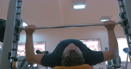 vzpírání : Low angle shot of a man doing strength exercise in a gym. Barbell bench press