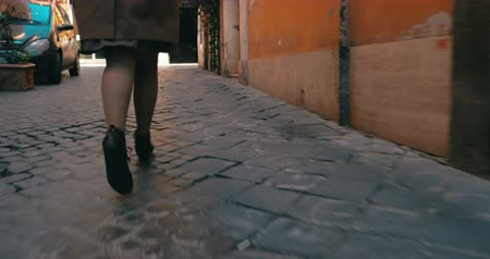 pursue : Steadicam and low angle shot of a woman running along the narrow cobblestone road. Its time to hurry up