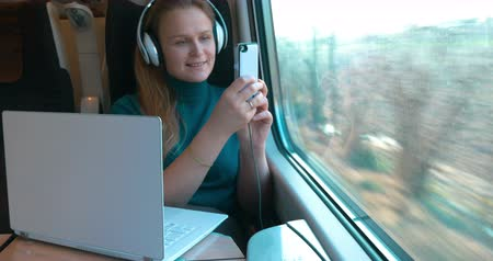 фото : Modern female passenger in the train.  She using laptop, listening to music in earphones and making photos of outside scene with mobile phone